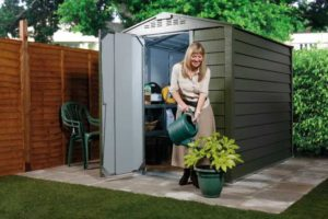 Woman watering plant in front of a garden storage system Trimetals